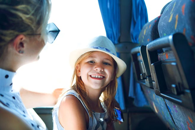 girl and mum smiling on bus