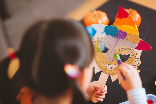 A toddler paints a witch mask for a Halloween craft activity