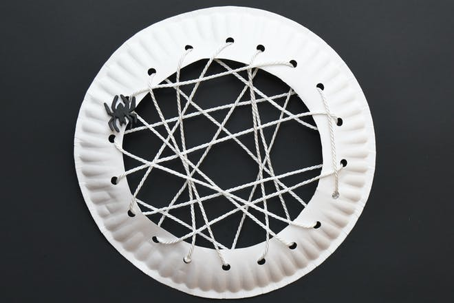 String threaded round the edge of a paper plate to make a spider's web for Halloween