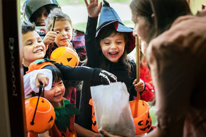 Group of children trick or treating dressed in Halloween costumes