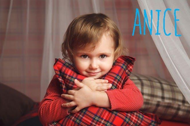 child holding red tartan pillow