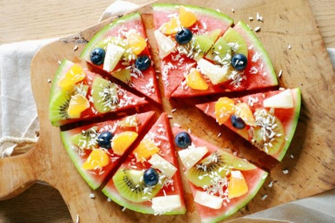Circle of watermelon cut into slices and decorated with fruit and coconut so it looks like a pizza