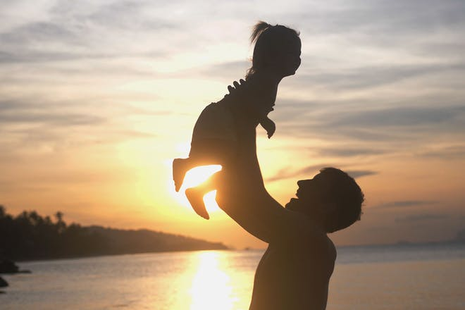 Silhouette of dad throwing daughter up in air by lake
