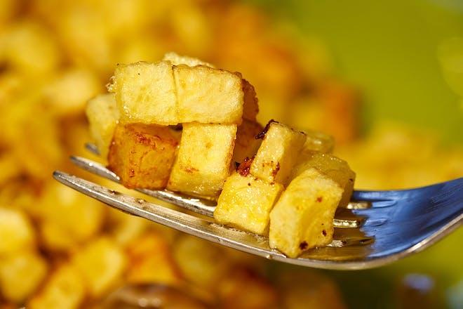 fried potato cubes on a fork