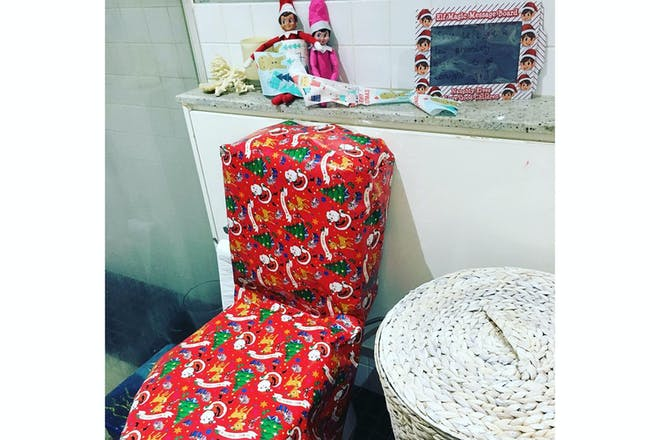 Elf on the shelf covered toilet in wrapping paper