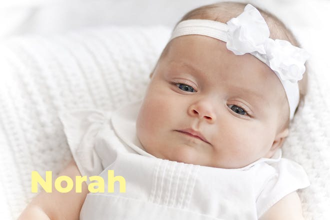 Baby in white dress and headband. Name Norah written in text