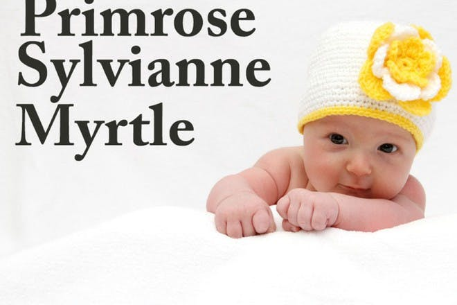 baby wearing white woolly hat with yellow flower