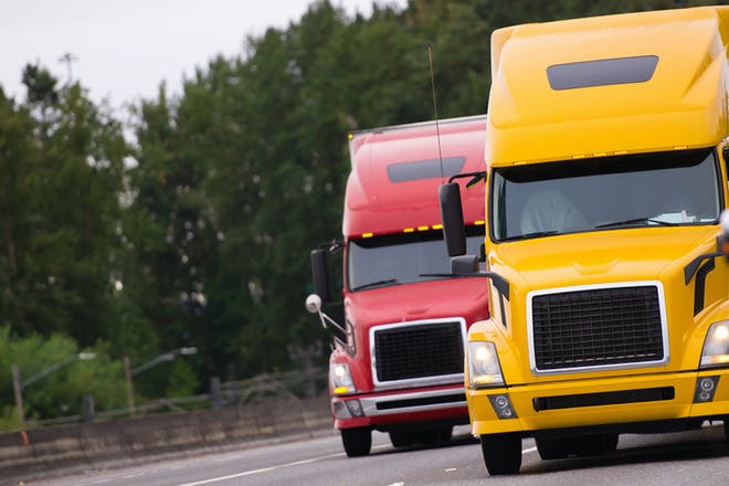 A red lorry and a yellow lorry on a motorway