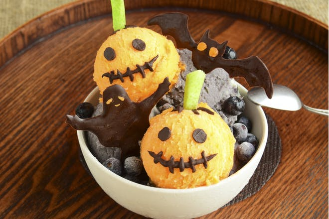 Scoops of orange halloween ice cream decorated to look like pumpkins and served in a bowl with chocolate ghosts and bats