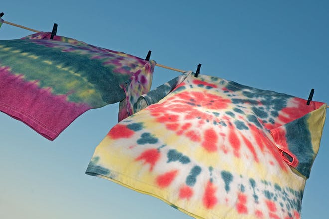 two tie dye T-shirts on a washing line