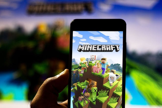 Hand holding phone with Minecraft video game on it