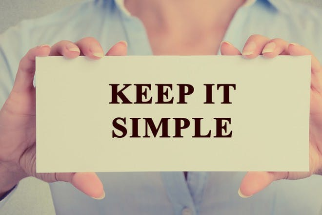 woman holding keep it simple sign