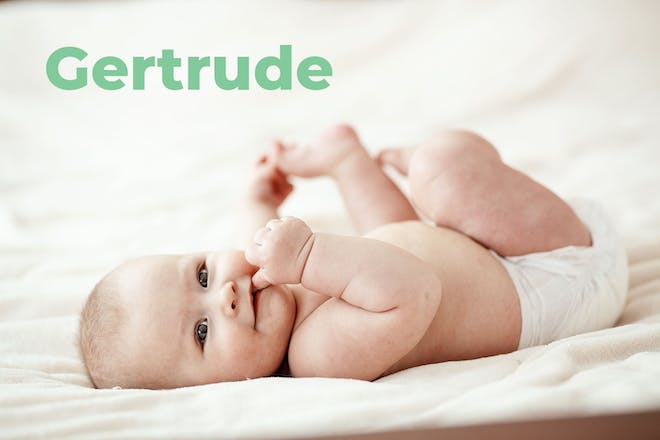 Baby lying on back holding foot. Name Gertrude written in text