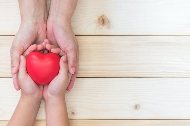 Adult and child hands with heart