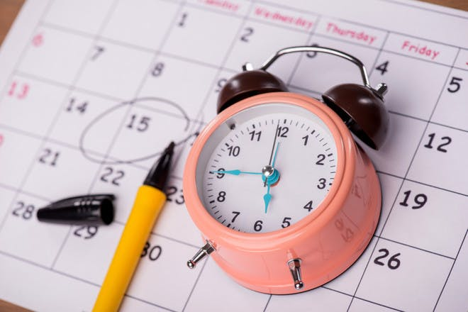 pink clock on calendar with pen marking date