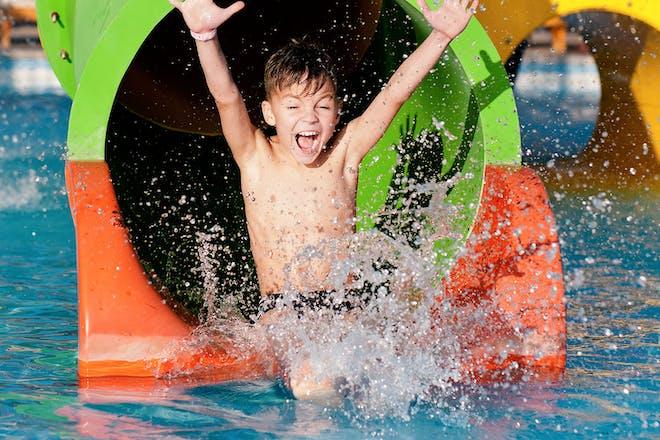 Boy going down water slide