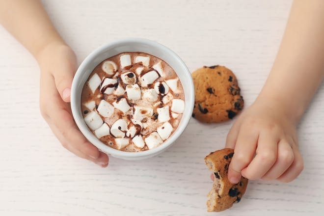 Kids hands holding cup of hot chocolate and cookie