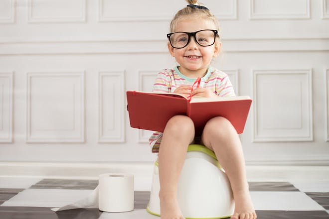 Toddler on potty with glasses and book