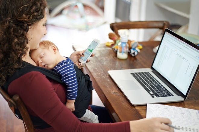 Woman on laptop with baby