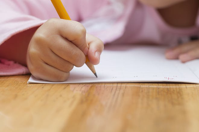 Child's hand holding pencil to paper