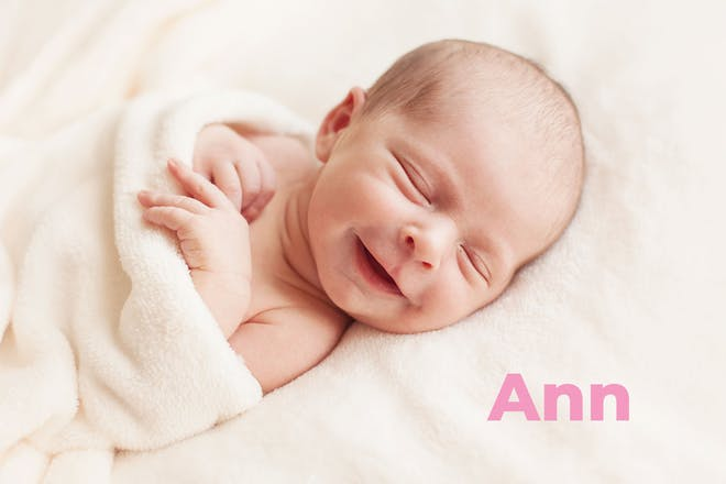 Smiling baby wrapped in towel. Name Ann written in text
