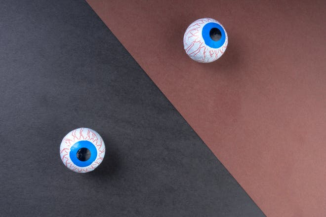 Two ping pong balls drawn on to look like blue-eyed eyeballs