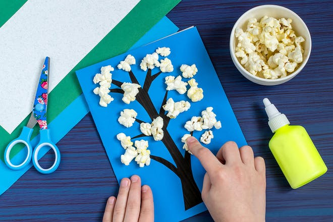 child sticking popcorn to card with tree drawn on