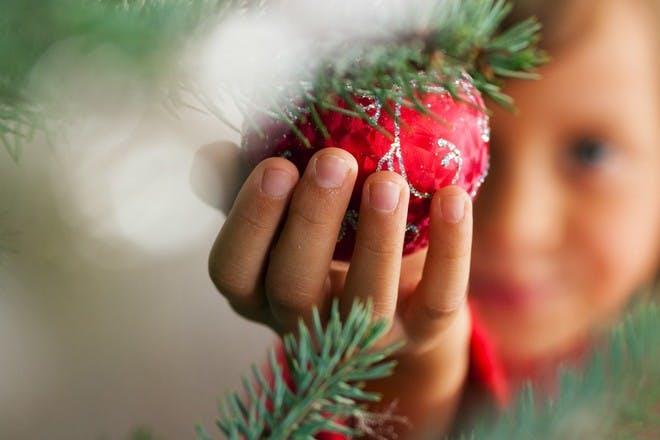child holding christmas decoration