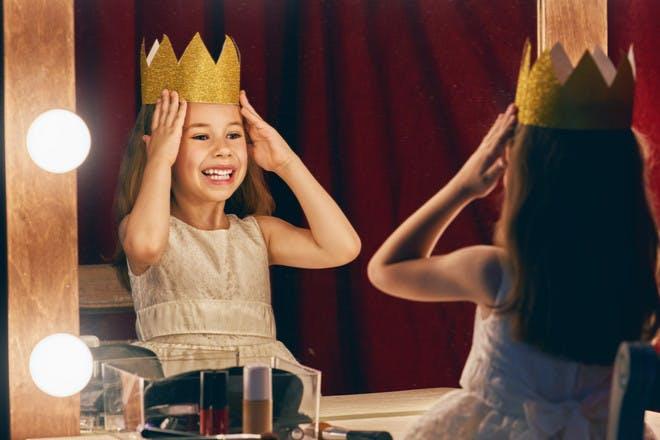 Little girl wearing crown in mirror
