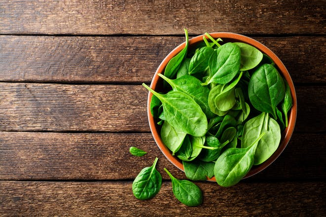 Fresh spinach leaves in a bowl on a wooden table.
