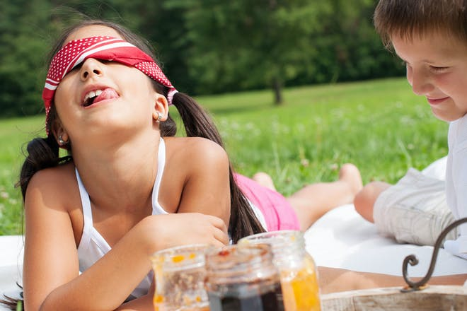 Blindfolded girl taste testing jam with brother outdoors