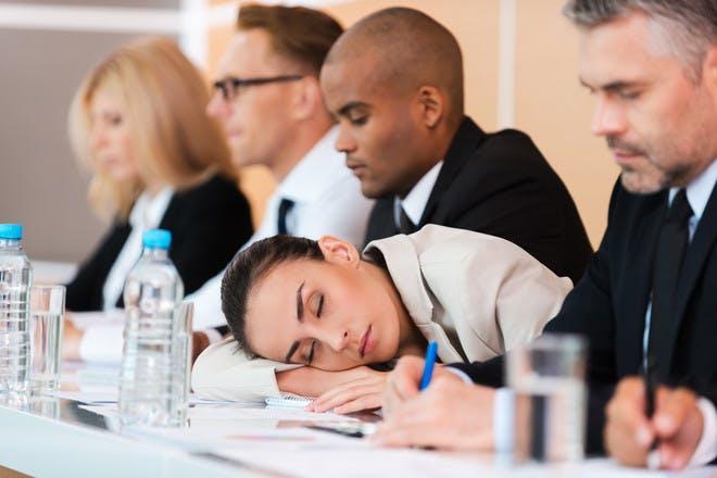 Woman sleeping on desk during meeting