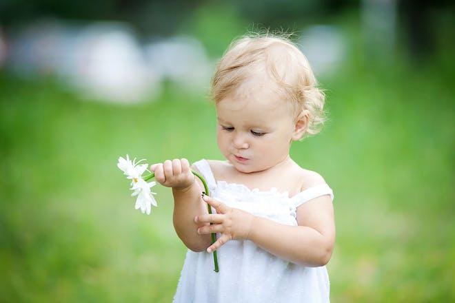 Toddler girl outside holding flower