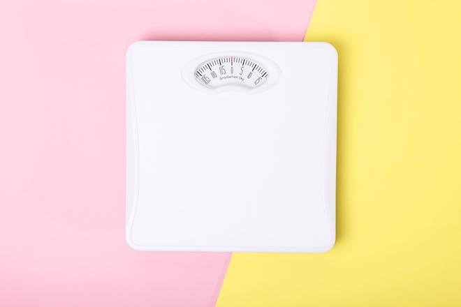 Weighing scales on a pink and yellow background
