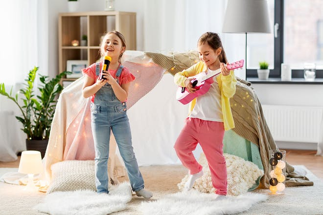 Two young girls with microphone and guitar performing in front room