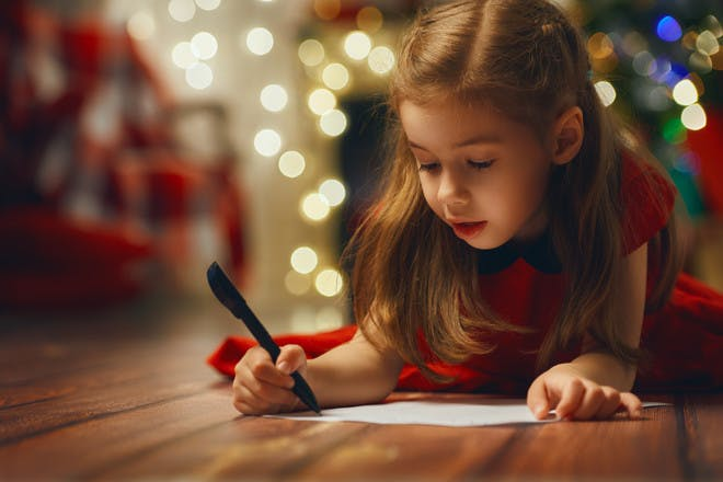 girl in red dress writing a letter to Santa