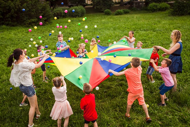 children bouncing balls on a parachute at party