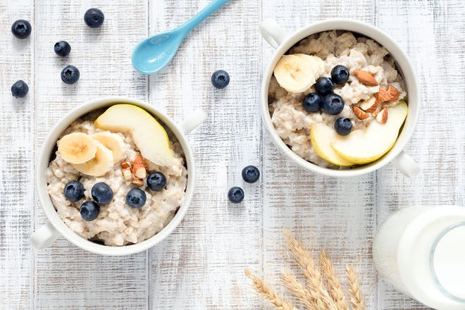 Two bowls of porridge with fruit and nuts