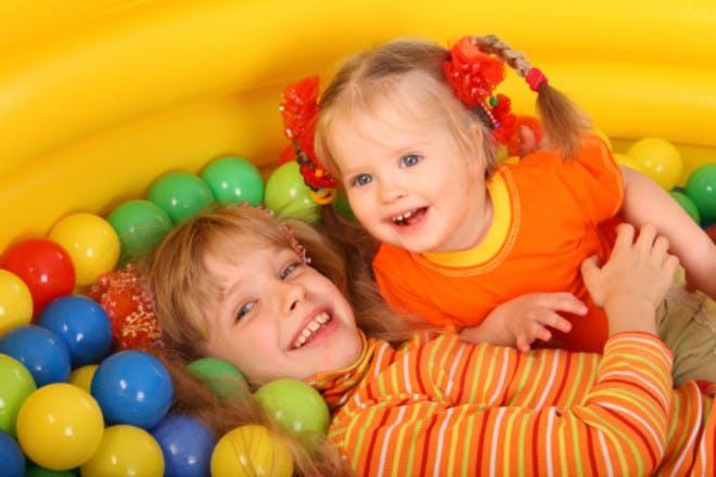 girls in a ball pool wearing orange