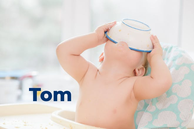 Baby in high chair tipping bowl of food into mouth. Name Tom written in text