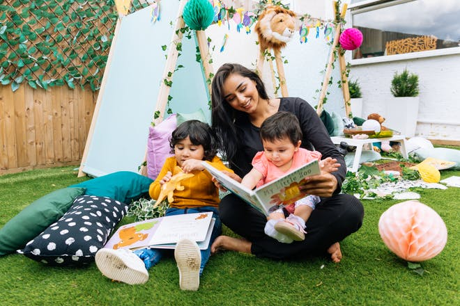 childminder with two children in garden