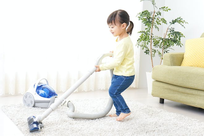 Young girl hoovering