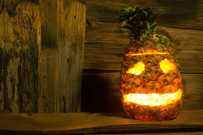 Carved pineapple Jack-o-lantern for Halloween