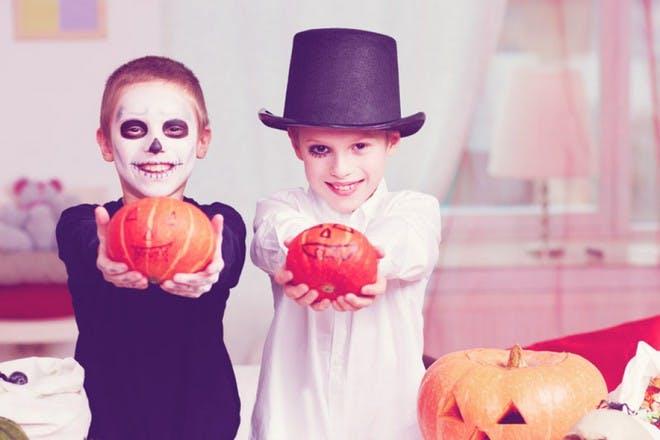kids on halloween with pumpkins