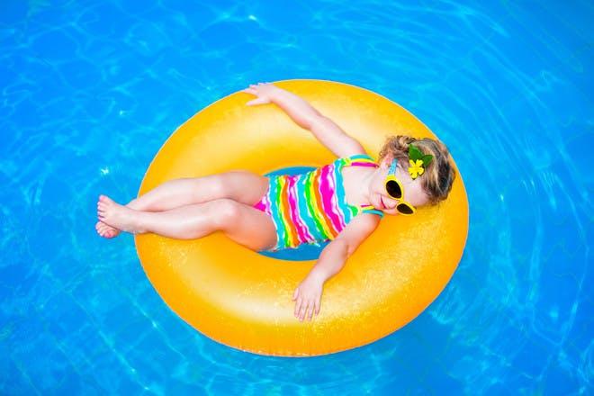 Child in pool doughnut float