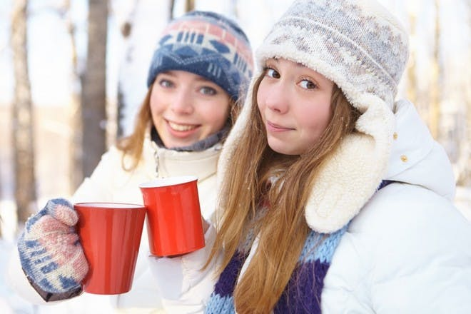 girl in winter woollies with hot chocolate