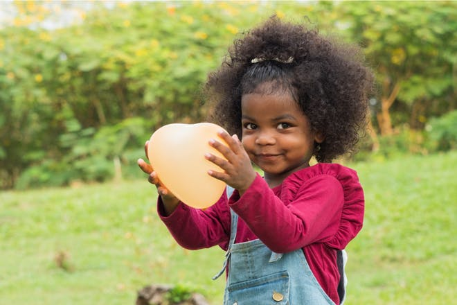 A toddler holds an orange balloon for Halloween party