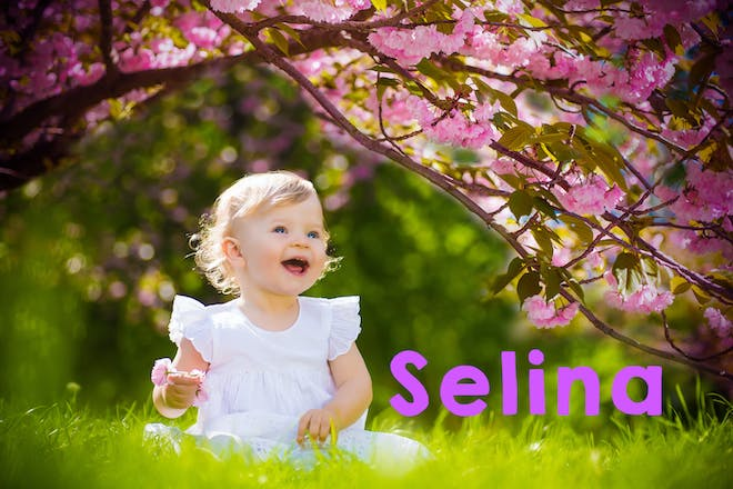 Baby playing in a garden beneath a pink blossom tree
