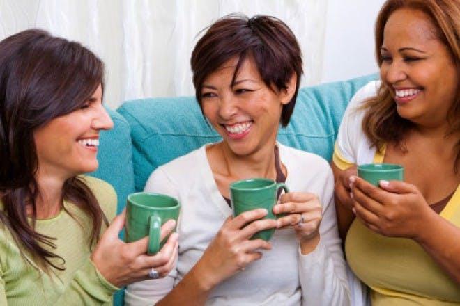 three women sitting on sofa drinking tea and chatting