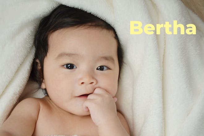 Baby lying on towel with finger in mouth. Name Bertha written in text
